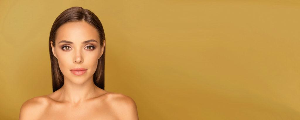 A latina model in a white bikini with her arms behind her head in a mustard gold room